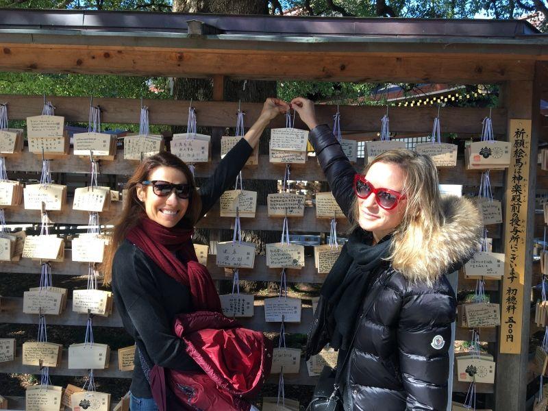Hanging their votive tablet at Meiji Jingu Shrine.