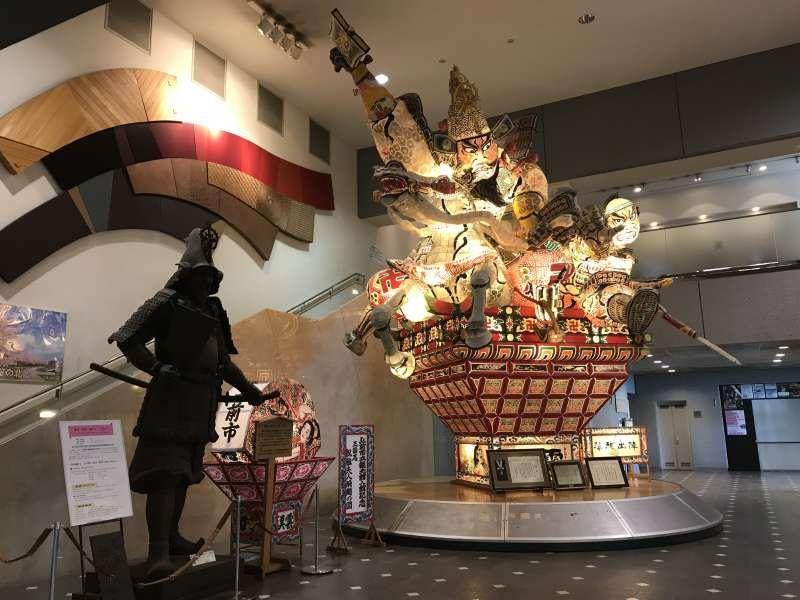 Hirosaki Tourist Information Center. A Neputa float and a statue of Tsugaru Tamenobu.