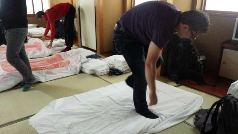 European tourists who are making a Japanese bed on Tatami floor in Shukubo, a hospicea guesthouse kept by a temple, at Zenkoji Buddist temple in Nagano prefecture.