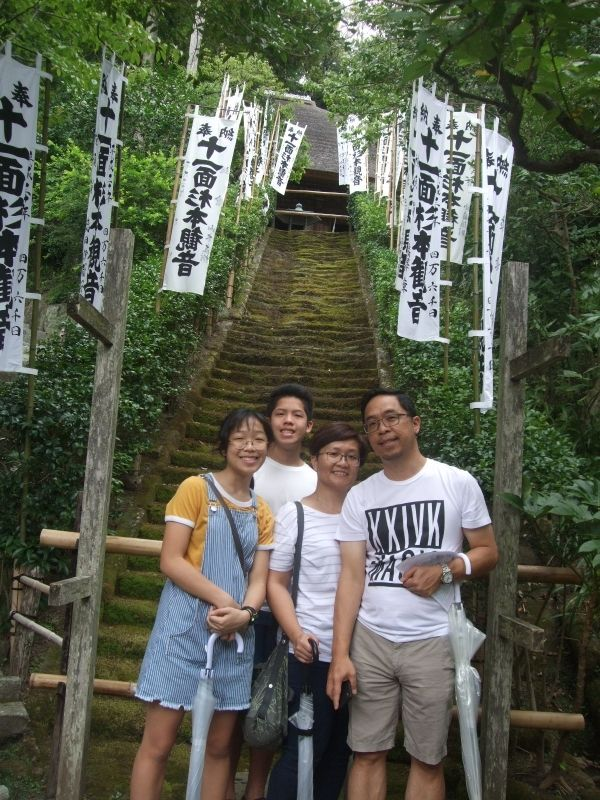 In front of the moss-covered staircase at Sugimoto Temple, the oldest Buddhist temple in Kamakura
