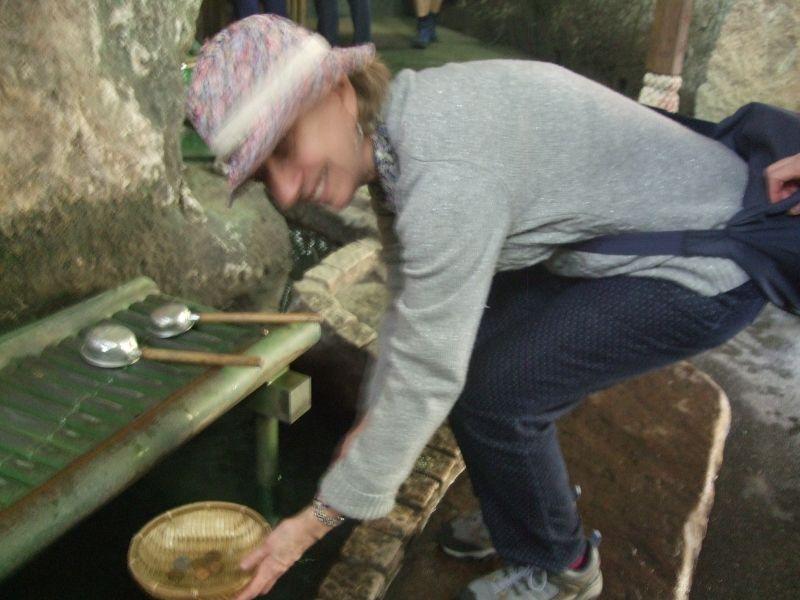 Washing and purifying coins with the fountain water at Zeniarai-Benten