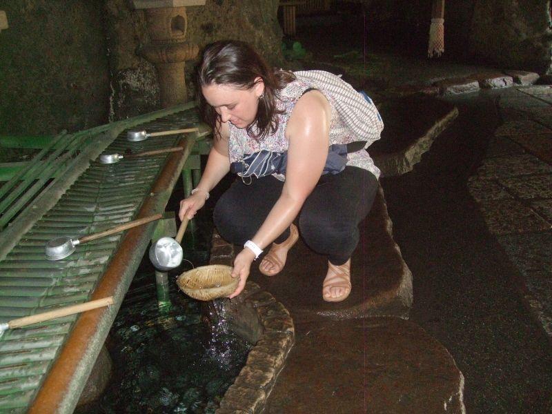 Purifying coins with sacred fountain water of Zeniarai Benten Shrine
