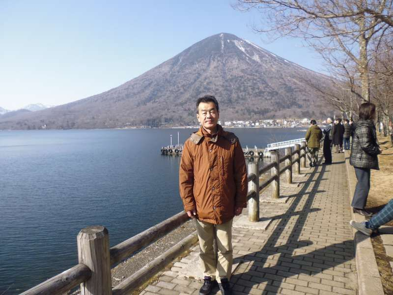 I am on the shore of Lake Chuzenji in Nikko in Tochigi Prefecture. Lake Chuzenji was formed by the eruption of Mt. Nantai which is seen in this photo in the background behind me.