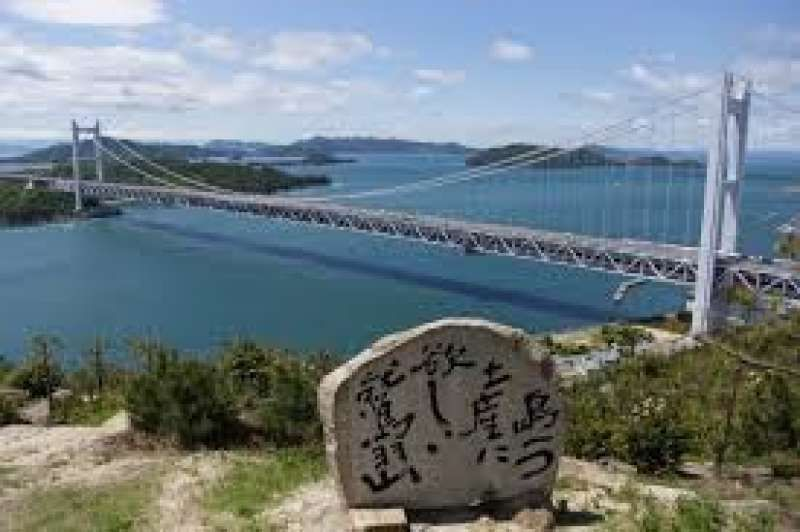 This is Seto Inland Sea and Seto ohashi Bridge.  It is in Kojima in Kurashiki City. You can see many small islands there. It is a very beautiful scenery. On the stone monument in the center is written the poem  meaning 'I am on the hill called Washuzan. I see many islands. They are beautiful.  I want to take one island  as a souvenir.' If you have time, you can enjoy cruising in the Seto Inland Sea from the port at the bottom of  Washuzan Hill.