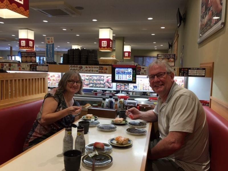 Wonderful couple exploring Kaiten-zushi, meaning circulating sushi, in Kyoto