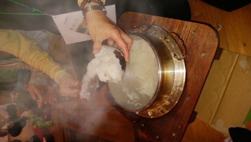 cooking koshihikari rice in a traditional iron pot.
