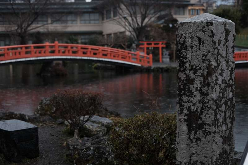 Wakutama Pond in the rain. The picturesque foot bridge is one of the popular photo spots in the shrine.