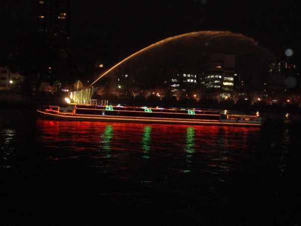 The fountain is squirting and aqua liner boat is cruising at night