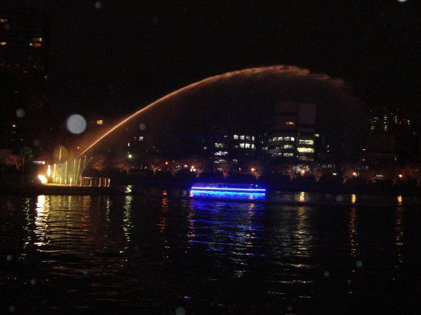 The fountain is squirting and a boat is cruising at night