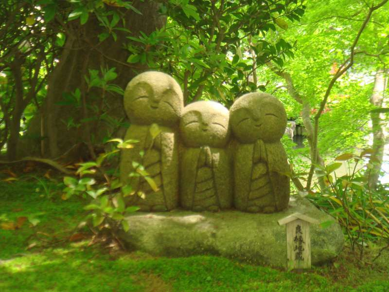 Simple Jizo statues set on the calm mossy green of Hasedera temple.