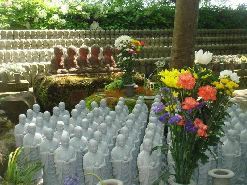 Visitors offer a prayer to the thousands of Jizo Bodhisattva.