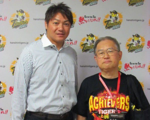 I am wearing a T-shirt from when the Hanshin Tigers won a victory in 2003 and the person on the left is Mr. Hamanaka who used to be a baseball player for the Hanshin Tigers who contributed to the victory.