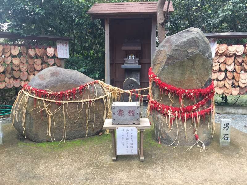 a match maker stones tied with red strings at Kuzuharagaoka shrine
