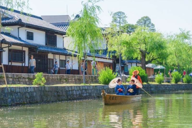 This stream is called Kurashiki River.You can ride this small boat and enjoy seeing Kurashiki Bikan historical are. A boatman rows a boat with a paddle.