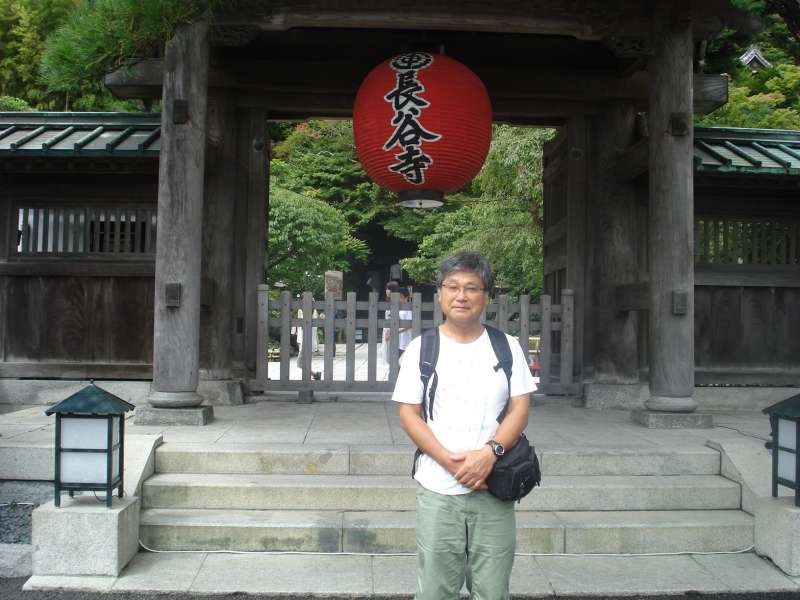 In front of the gate of Hase Temple. In this temple, there is a cave where the image of Benzaiten, or the Goddess of Eloquence, Music, and Art, and those of sixteen Douji, or the attendants of Benzaiten, are laid along the path for visitors. At the end of the steps, a huge golden statue, Hase Kannon, or Hase Goddess of Mercy, stands overlooking visitors. The terrace on which the Goddess is located commands a wide open view of the Yuigahama Beach.