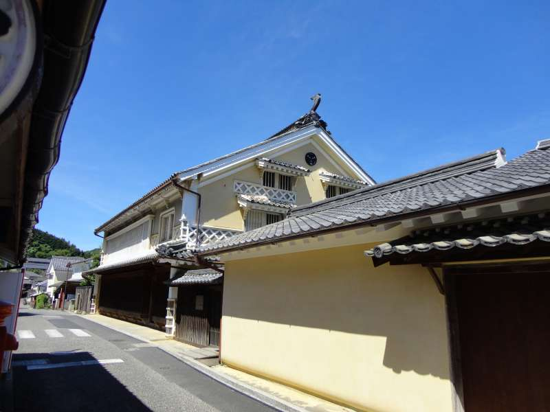 Houses with thick cream-colored plastered wall continue along the street of the Yokaichi & Gokoku Historic District Preservation Zone prospered as a manufacturing center of Japanese wax.