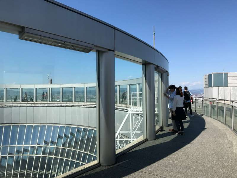 Umeda Sky Building. The open air observation corridor is also nice.  It is 170 meters high. Visitors can touch breeze air and enjoy 360 degree views.