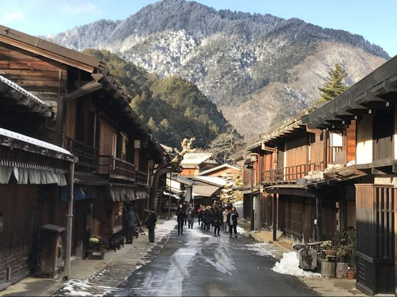 Visitors stroll around the traditional wooden-house street in Tsumago-juku