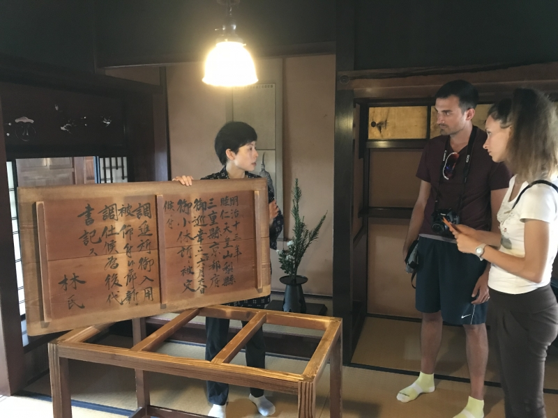 A female member of staff is explaining the record relating to the short stay of the Meiji emperor in English, which was written on the back of the table.