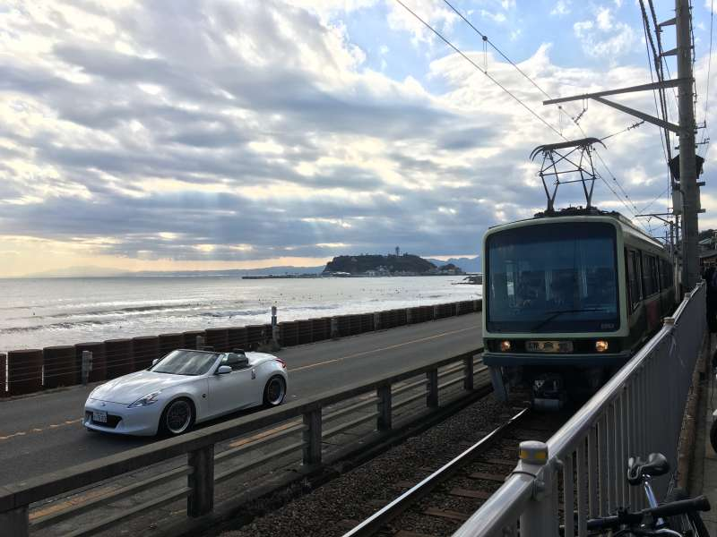 Distant view of Enoshima island with Enoden train at around Kamakura Koko Mae station