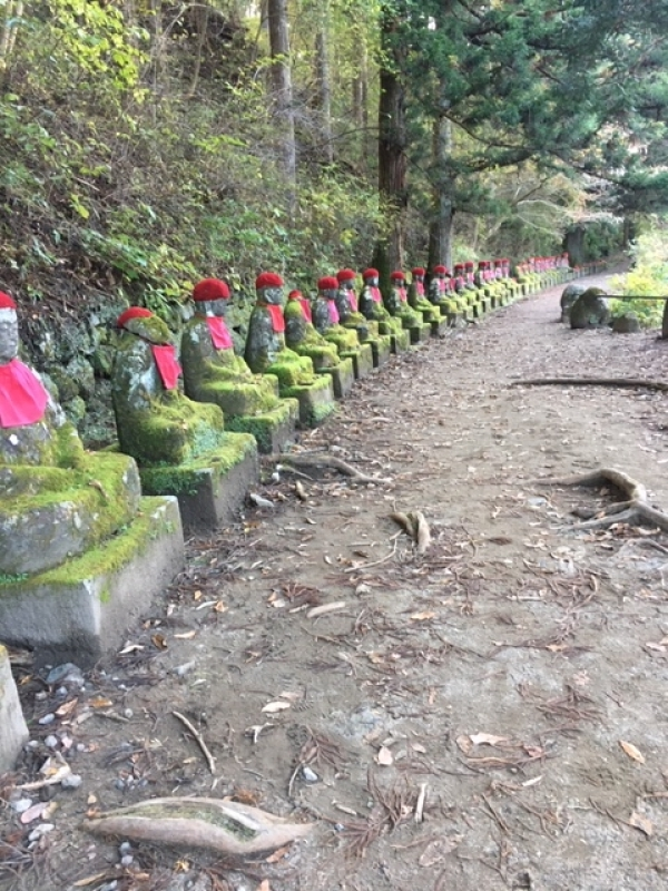 Kanmongafuchi Abyss, a row of many Jizo bodhisattvas in the quiet grove along pure cerulean streams