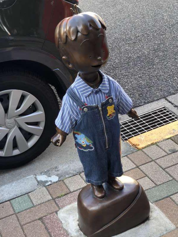 Cute manga character doll standing along Kagurazaka hill