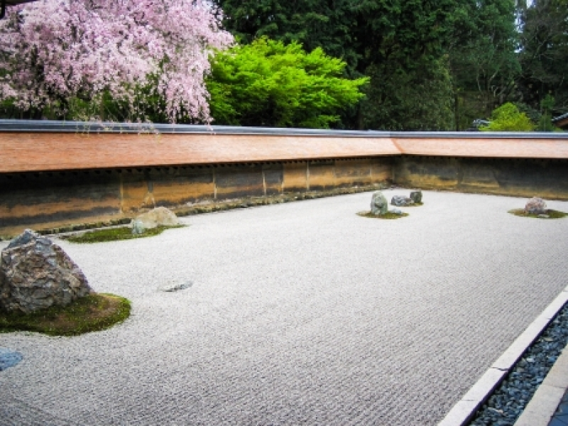 Ryoanji Temple...Rock garden enclosed by earthen walls and verandah and 15 rocks rising up from white sand suggesting mountains in sea