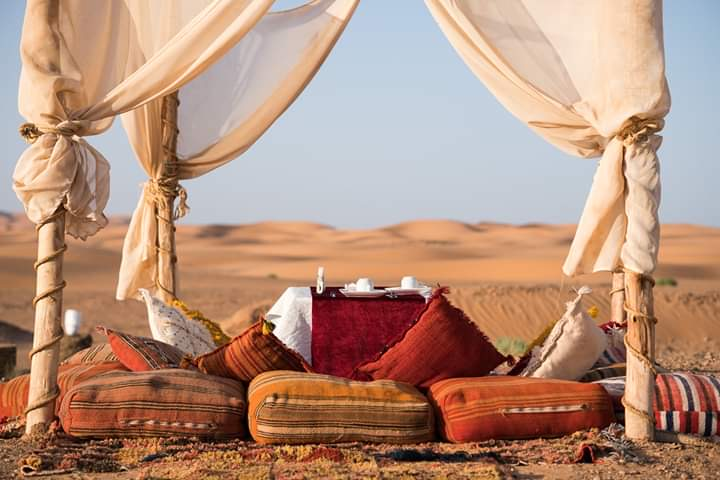 romantic siiting in the sahara desert to watch sunset or sunrise