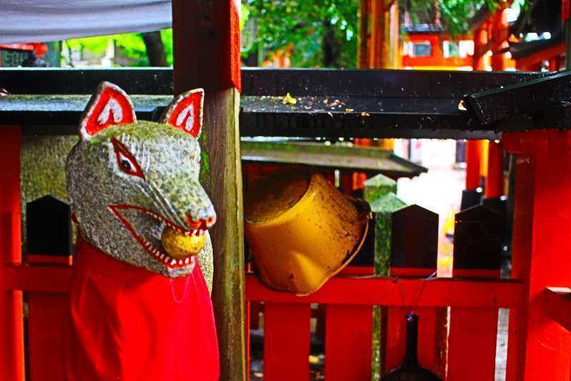 Fushimi Inari Shrine. Byakko. Gods' messenger fox holding a stroll in its mouth.