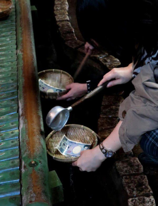 Zeniarai Benten.  Pouring sacred water on to bills and coins in a cave