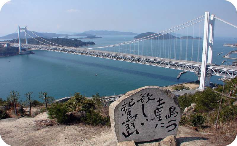 This is Seto Inland Sea and Seto ohashi Bridge . On the stone monument in the center is written the poem meaning 'I am on Washuzan Hill. I see many islands. They are beautiful. I want to take one island as a souvenir.'