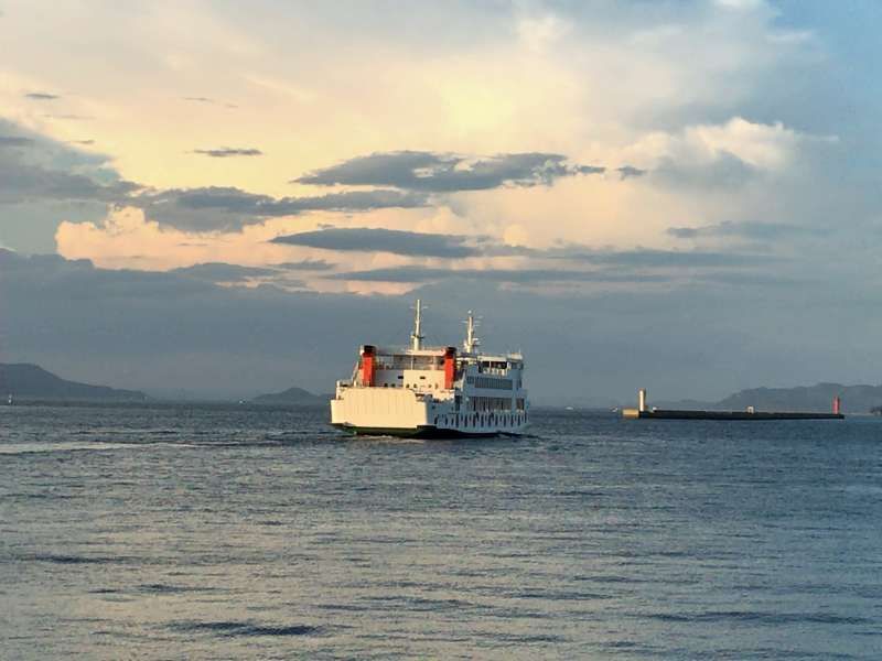 A ferry connecting Takamatsu and Naoshima, with a beautiful sunset behind
