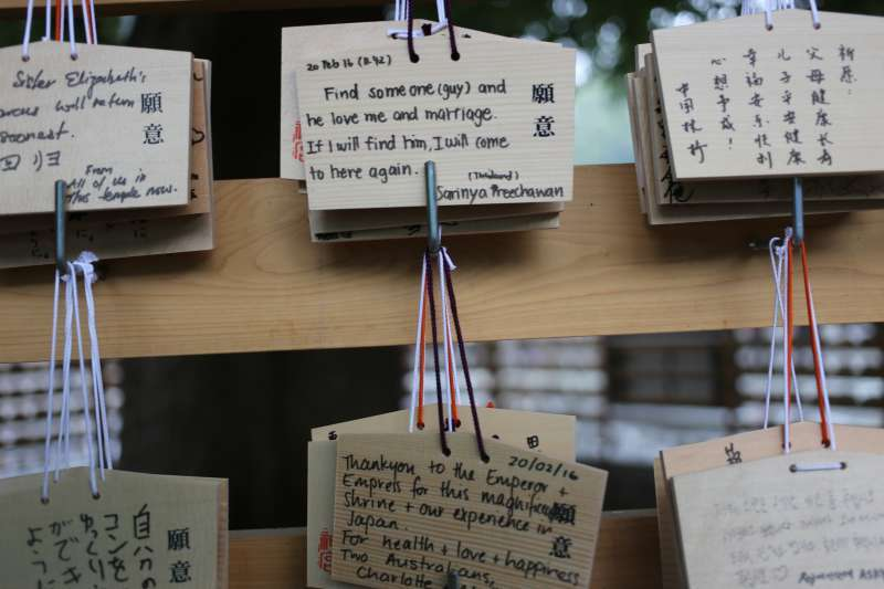 Ema Boards or Japanese wishing plaques donated by foreign tourists at Meiji Shrine. All you have to do is to write your wishes in your language of choice on a wodden plaques and tie them onto the prayer wall.