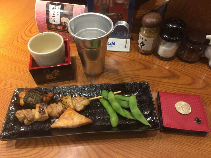 At the standing Sake bar which is owned by a Sake brewery. Many kind of sake and snacks are tried with affordable prices. Photo shows one coin set menu with  JPY500,