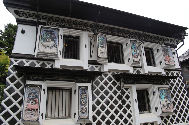 Saffron Wine Storehouse with colorful reliefs of zodiac animals on the plaster wall is located just across the street from Yoshinogawa sake brewery in Settaya district where the brewing of