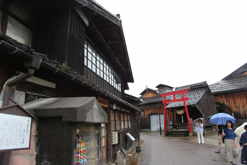 Koshino Murasaki soy sauce brewery wooden building on the left side is on ancient Mikuni Highway protected by local Inari Shrine with vermillion-colored torii gate on the right side.