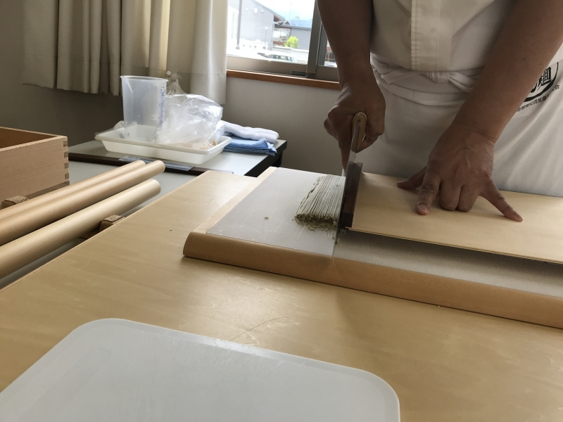 Cutting buckwheat noodle with special soba knife pushing slightly with upper plate.