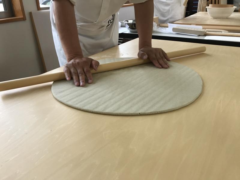 With wooden poll, extend buckwheat dough further.
