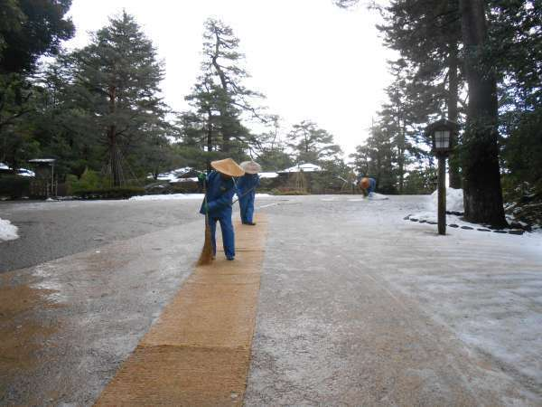 Sweeping the snowy path at Kenrokuen garden.