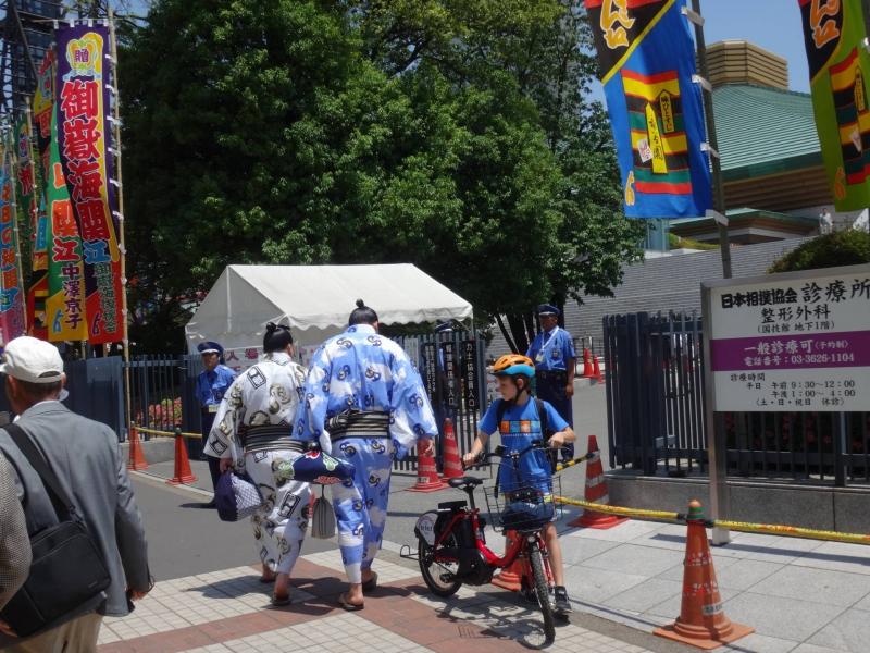 Sumo wrestlers walking in front of a sumo arena, Ryogoku Kokugikan
