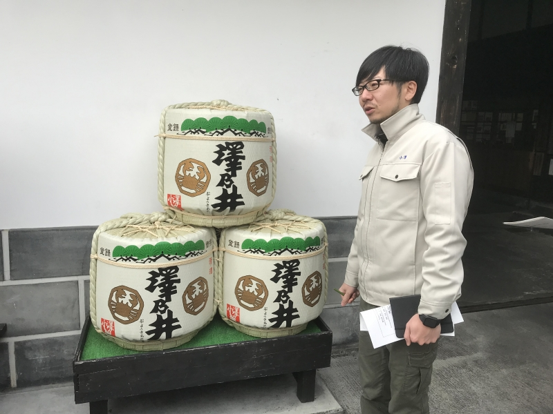 Young president of the brewery,  Ozawa-san, and sake casks
