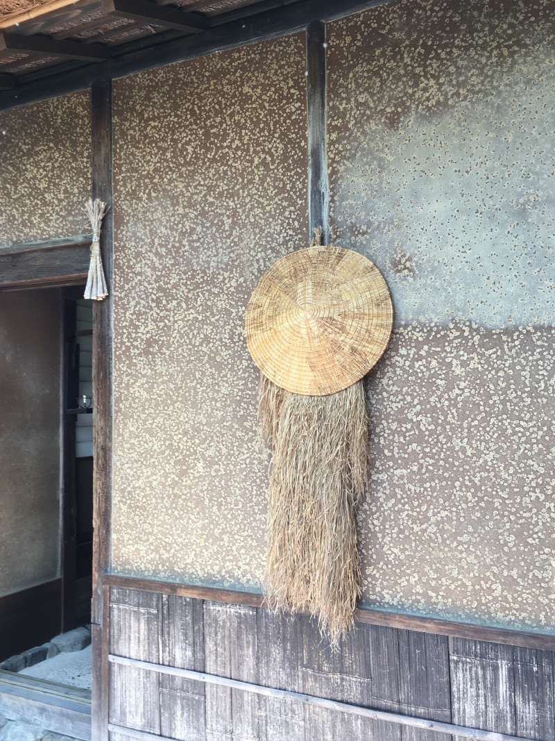 At the door, there are a straw raincoat and a straw lampshade hat which showed that the resident was at home.